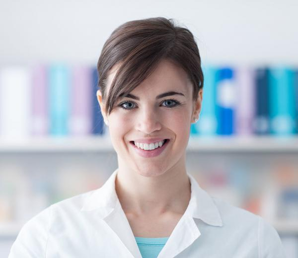 Smiling young doctor posing and looking at camera, healthcare professionals